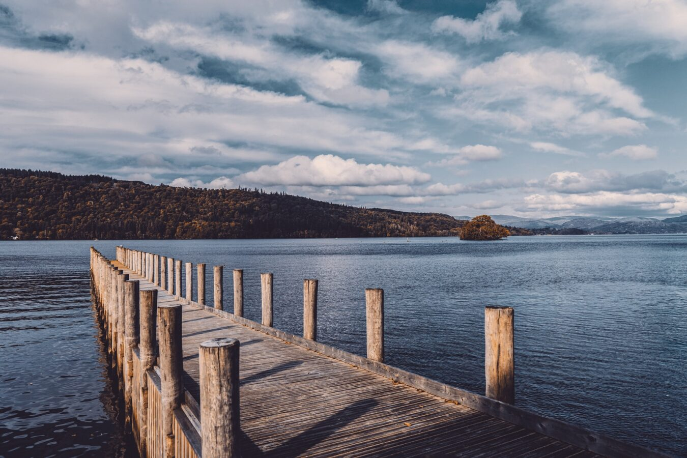 brown wooden dock on blue sea under white clouds during daytime